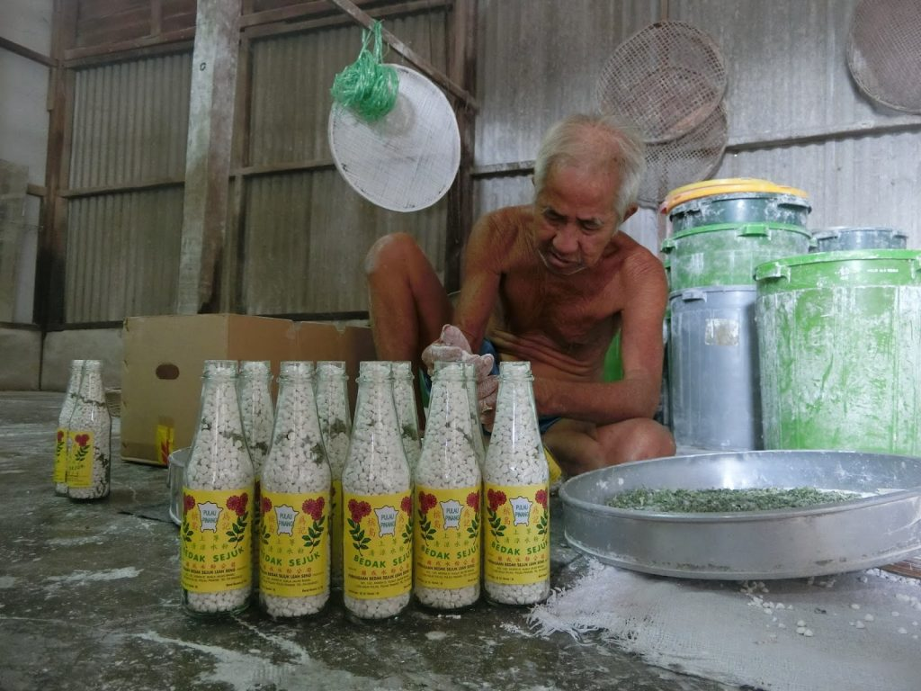 The founder of Lean Seng Bedak Sejuk, Yeoh Keng Beng packaging the bedak sejuk.